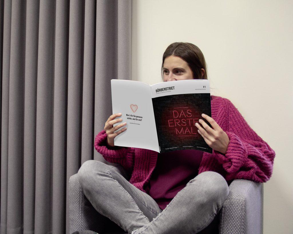 Juliane sitzt in einem Sessel und liest die Börbenstriet