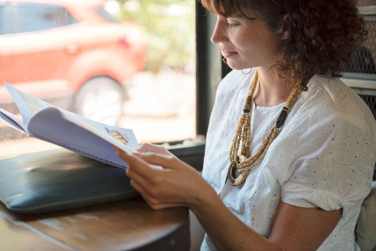 Junge Frau liest im Café ein Magazin